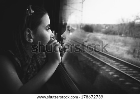 Little girl looking through window. She travels on a train.  - stock photo