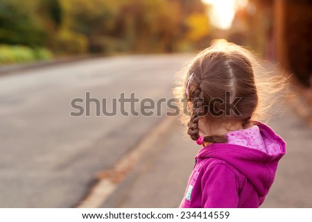Little girl looking to cross the street. Rear view. - stock photo
