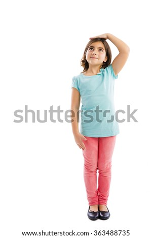 Little girl looking up and checking her size - stock photo