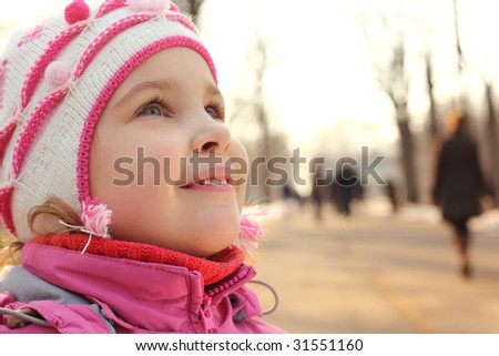 Little girl looking up and people outdoor
