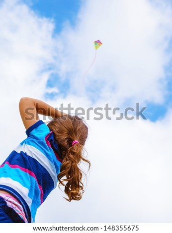Little girl looking up in the sky on beautiful colorful air kite, rear view, enjoying summer game, flying toy, happy childhood concept - stock photo