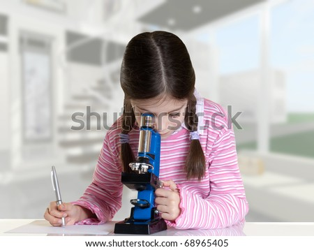 little girl looking with microscope in school laboratory - stock photo