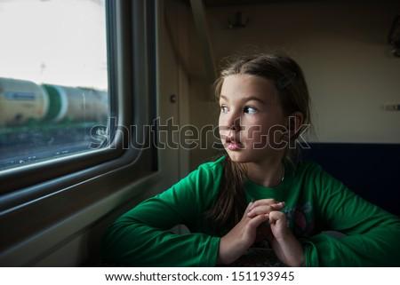 Little girl looks in train window. - stock photo