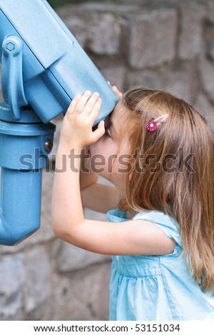 Little girl looks intently through binoculars at the world around her. - stock photo