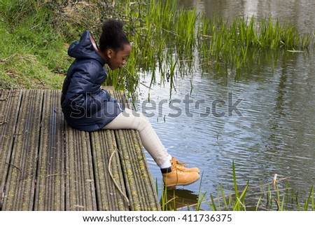 Little girl looks into pond with feel hanging over