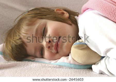 little girl lying in bed just before falling asleep - stock photo