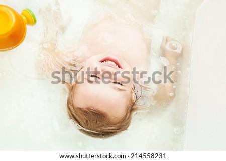 Little girl lying in the bathtub - stock photo
