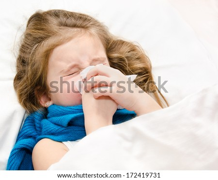 Little girl lying in the bed blowing her nose - stock photo