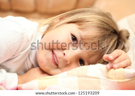 Little girl lying on a bed and smiling