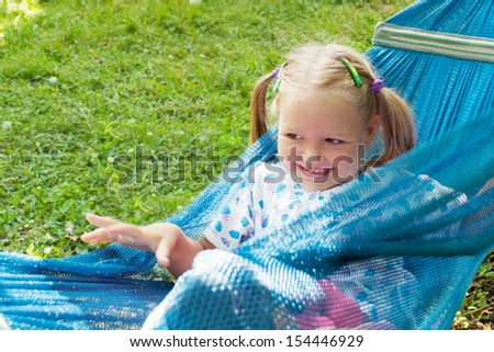 little girl lying on a hammock and smiling - stock photo