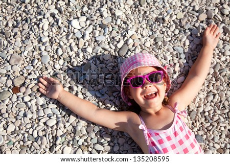 little girl lying on a pebble beach - stock photo