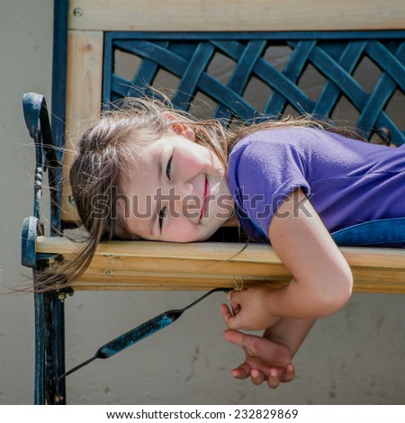 Little girl lying on an outside bench, looking at the camera and smiling. - stock photo