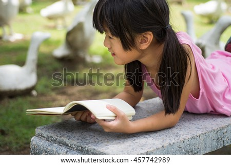 Little girl  lying on bench and read book in the park - stock photo