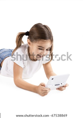 Little girl lying on floor playing a video-game - stock photo