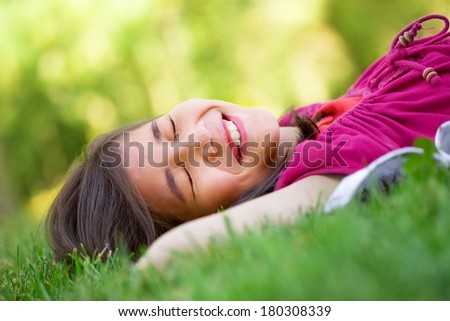 Little girl lying on grass lawn smiling with eyes closed, laughing