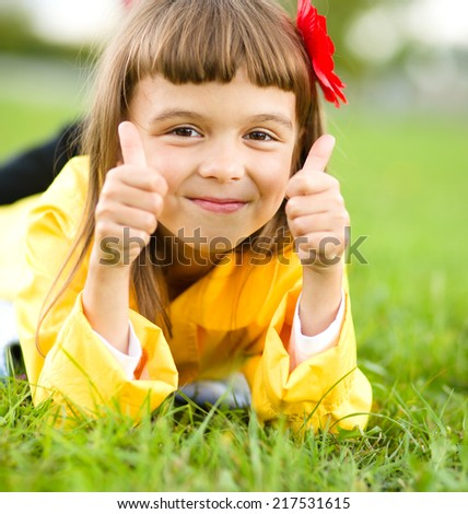 Little girl lying on green grass is showing thumb up gesture - stock photo