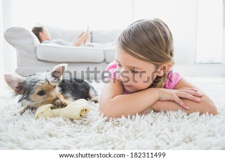 Little girl lying on rug with yorkshire terrier at home in the living room - stock photo