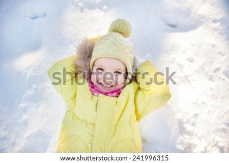 Little girl lying on snow - stock photo