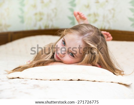 Little girl lying on the bed. - stock photo