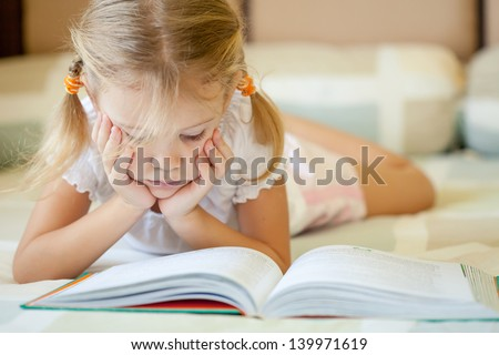little girl lying on the bed and reading a book - stock photo