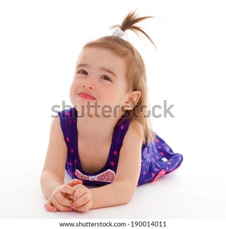 Little girl lying on the floor - stock photo