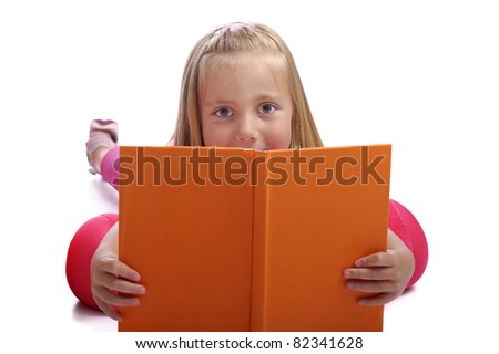 little girl lying on the floor reading a book. isolated on white background - stock photo