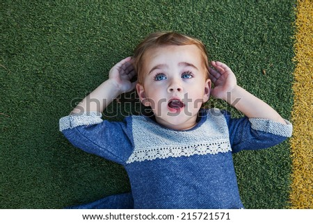 Little girl lying on the football field looking at the sky - stock photo