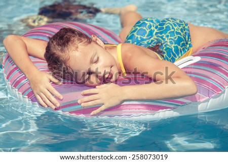 little girl lying on the  inflatable rubber circle  in the swimming pool at the day time - stock photo