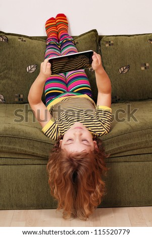little girl lying upside down on bed and play with tablet - stock photo