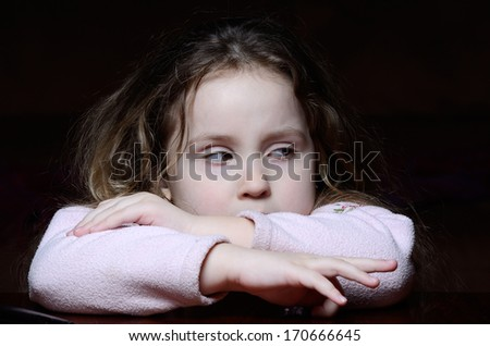 Little girl makes a face at table - stock photo