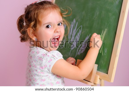 Little girl makes a funny face as she draws on the blackboard - stock photo