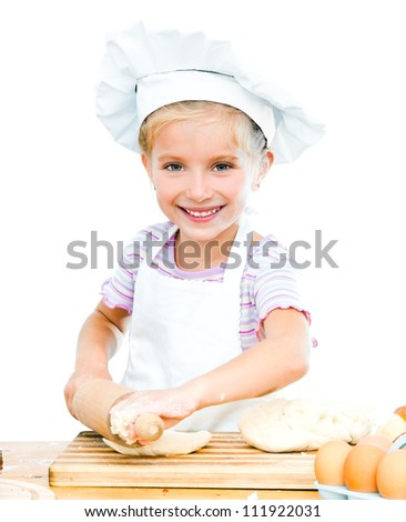 Little girl makes dough on kitchen with rolling pin - stock photo