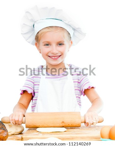 Little girl makes dough with rolling pin on a white background - stock photo