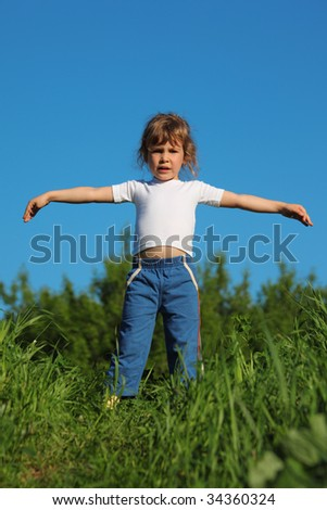 Little girl makes gymnastic in grass