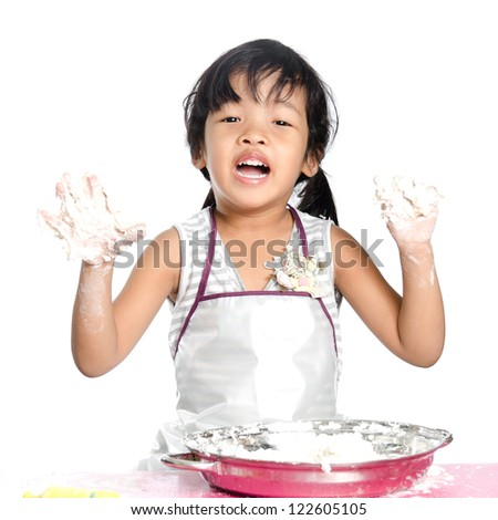 Little girl makes play dough on white background. - stock photo