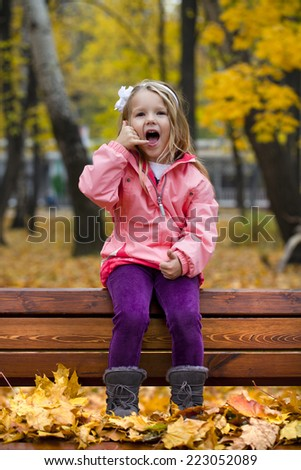 Little Girl making a call me gesture, against background of autumn park - stock photo
