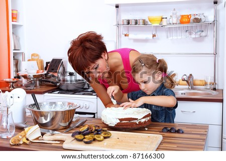 Little girl making a fruit cake with her mother - stock photo