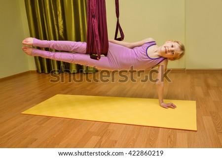 Little girl making aerial yoga exercises, indoor, fly yoga - stock photo