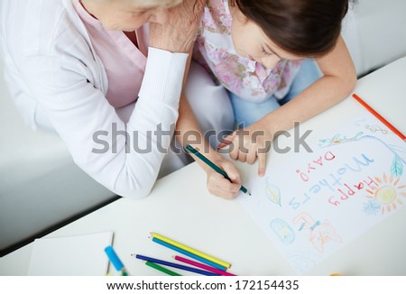 Little girl making card for her mom with her grandmother near by - stock photo