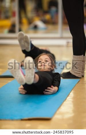 Little girl making exercises on floor mat in bodysuit - stock photo