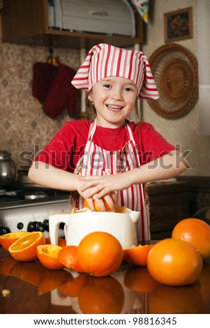 Little girl making fresh and healthy orange juice with kitchen appliance