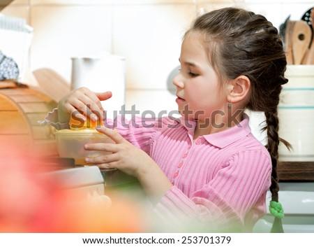 Little girl making fresh fruit juice - stock photo