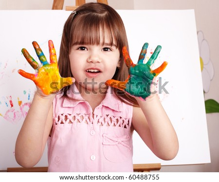 Little girl making hand-prints with paint. - stock photo