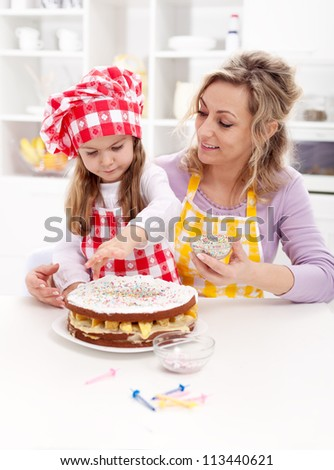 Little girl making her first fruit cake - together with her mother - stock photo