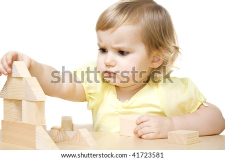 Little girl making house from wooden blocks
