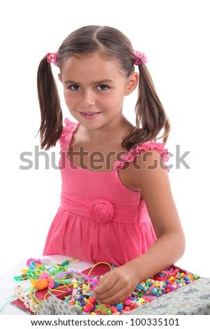 Little girl making jewelry - stock photo