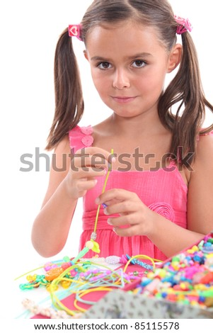 Little girl making necklace - stock photo