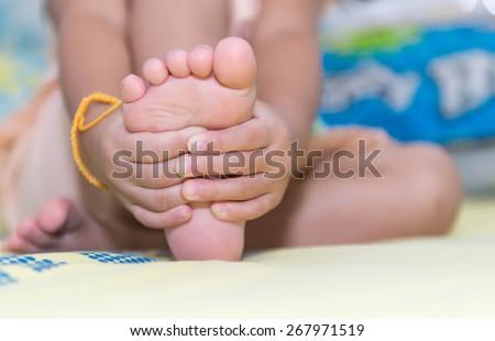 little girl massaging his aching feet - stock photo