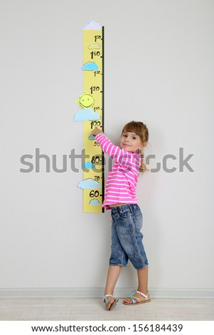 Little girl measuring height against wall in room - stock photo