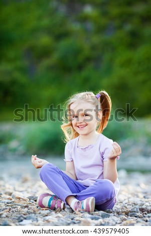 Little girl meditates, outdoor - stock photo